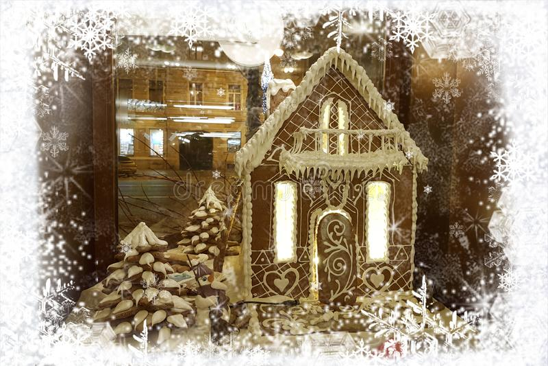 Julhälsningkort med pepparkakahuset och snögubbe i ramen av vita snöflingor på bakgrund av nattstaden arkivfoton