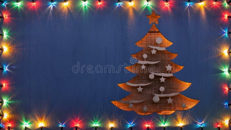 Julhälsningkort med xmas-trädet och dekorativa ljus royaltyfria bilder