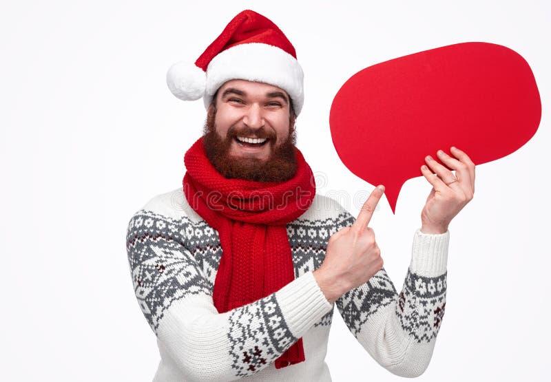Julhipsteren santa som rymmer en röd bubbla, tänkte arkivfoton