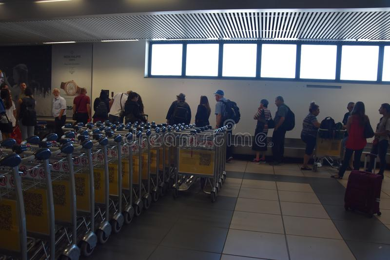 2016 julho Verona Italy - turistas e carros da bagagem no aeroporto de Verona imagem de stock