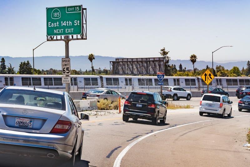 Juli 13, 2019 Hayward/CA/USA - motorvägingång i östligt San Francisco Bay område; BART Bay Area Rapid Transit drev som in passera royaltyfri bild