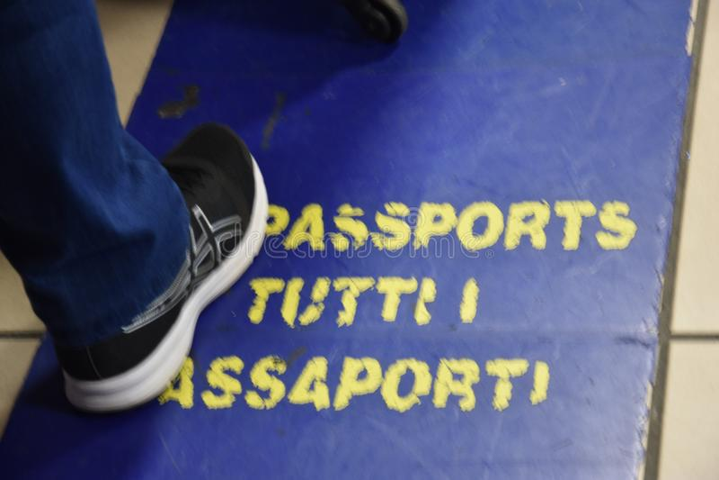 2016 Juli Italië - Mannelijk been in het paspoortcontrole van tennisschoenpassen bij de luchthaven royalty-vrije stock foto
