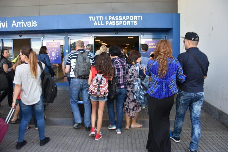 2016 Juli Italien - folket passerar passkontroll på flygplatsen royaltyfria foton