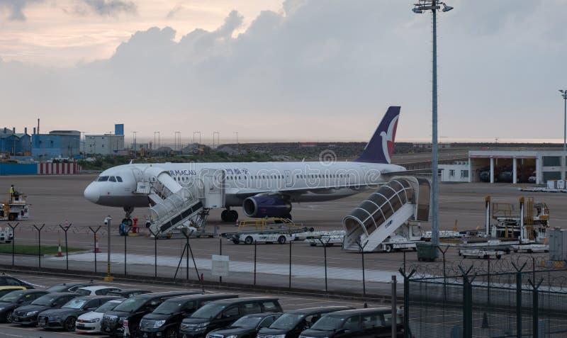 02 Juli, 2018 Macao internationell flygplats Passagerareflygplan som parkeras på flygplatsen Kommersiell jet med solnedgång royaltyfri fotografi