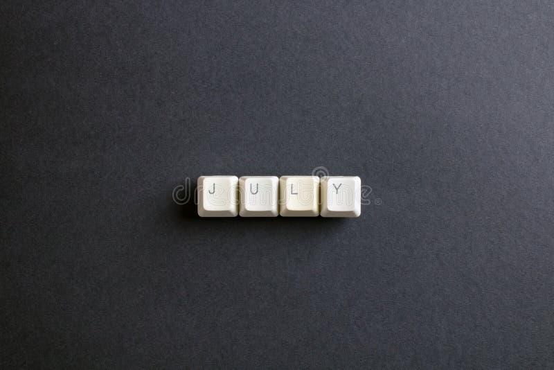Juli-Monatswort wird mit Computerschlüsselknopf geschrieben Flache Lage V stockfotografie