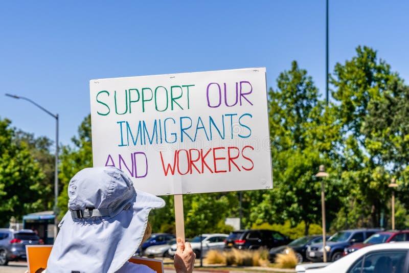 Juli 26, 2019 Palo Alto/CA/de V.S. - Protesteerder die een teken met het bericht 'Steun houden onze immigranten en arbeiders ' stock fotografie
