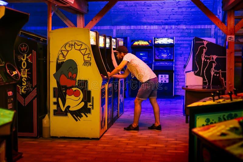 Juli 25, 2017 - Prague, Tjeckien: Den unga mannen med locket spelar ivrigt en gammal man för gallerivideospelPac II royaltyfri fotografi
