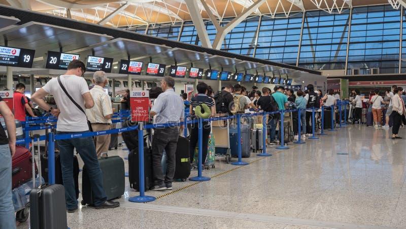 15 Juli, 2018 Pudong flygplats, Shanghai, Kina Bilden av passagerare kontrollerar in på incheckningsdisken på arkivfoton