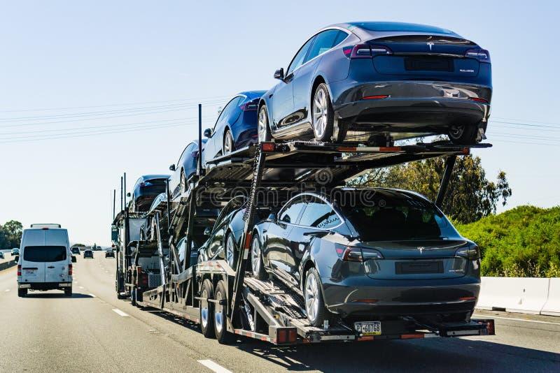 4. Juli 2019 Redwood City/CA/USA - Autotransporter trägt Tesla Model 3 neue Fahrzeuge entlang der Landstraße in San Francisco Bay lizenzfreies stockfoto