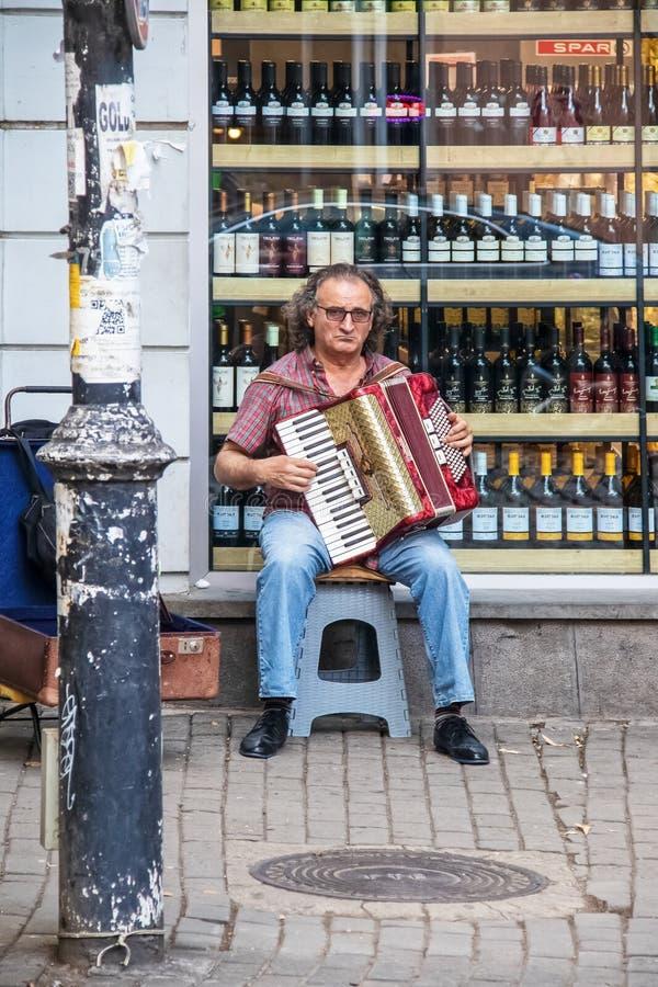 15 juli Tbilisi Georgië - Mensenzitting op kruk voor wijnopslag het spelen harmonika in Oude Stad royalty-vrije stock afbeeldingen