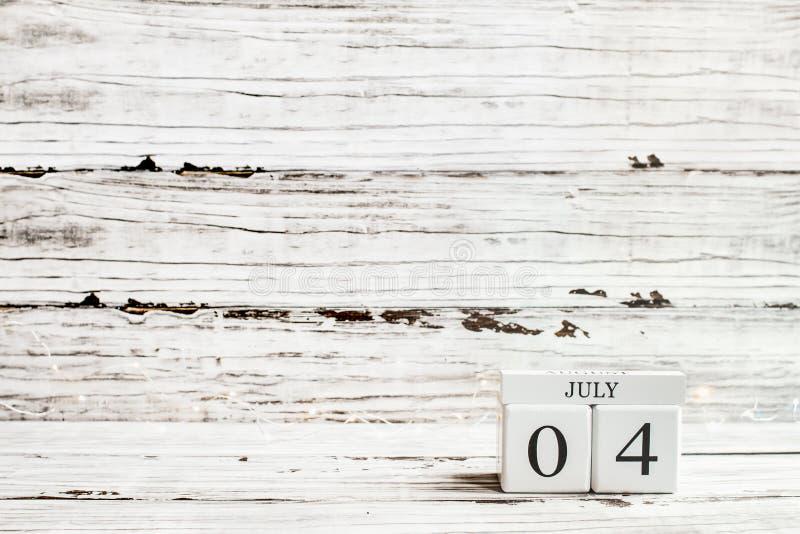 Juli 4th kalenderkvarter mot lantlig vit bakgrund arkivfoton