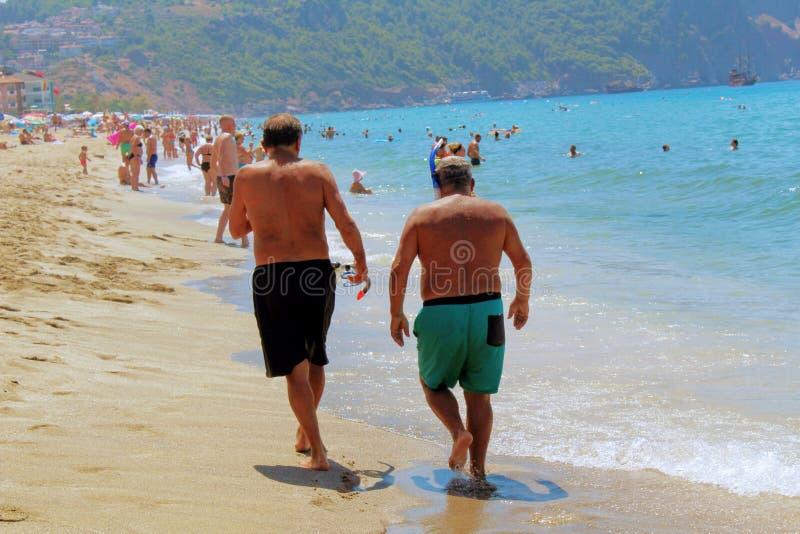 Juli, 2017 - Twee bejaarden loopt langs de kust in Cleopatra Beach Alanya, Turkije royalty-vrije stock fotografie