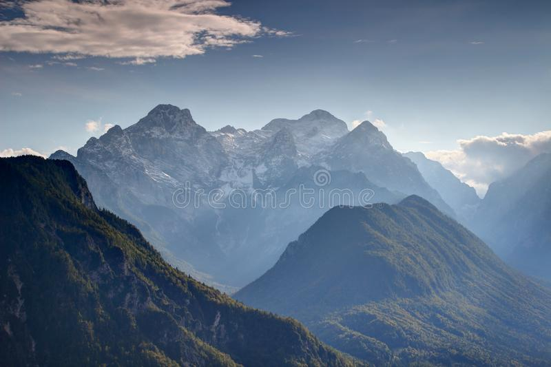 Julian Alps deep valleys in autumn haze with snowy Triglav peak. Steep walls of deep Vrata Kot valleys in autumn haze with snowy Triglav Rjavina and forested royalty free stock images