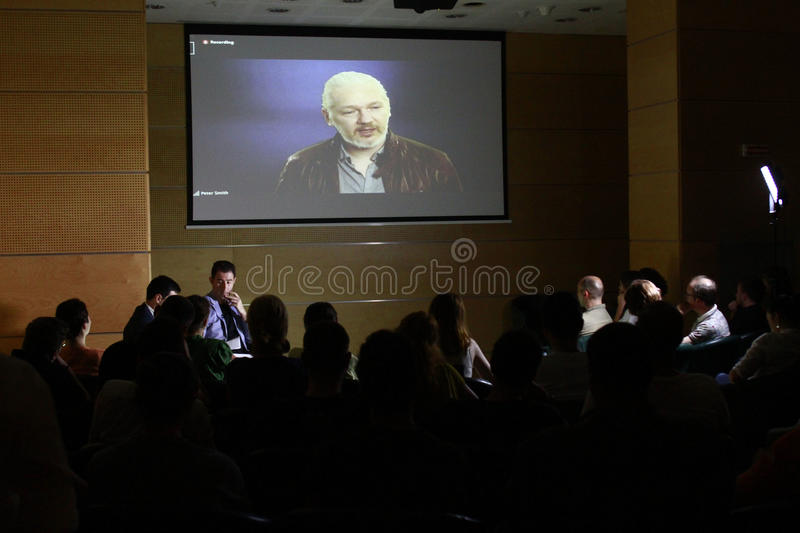 Julian Assange conference. BUCHAREST, ROMANIA - MAY 19, 2015: WikiLeaks founder Julian Assange speaks via a web conference about press freedom and democracy stock image