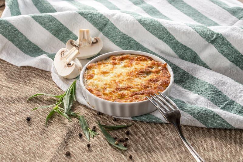 Julienne с грибами и расплавленным сыром на серой скатерти стоковая фотография