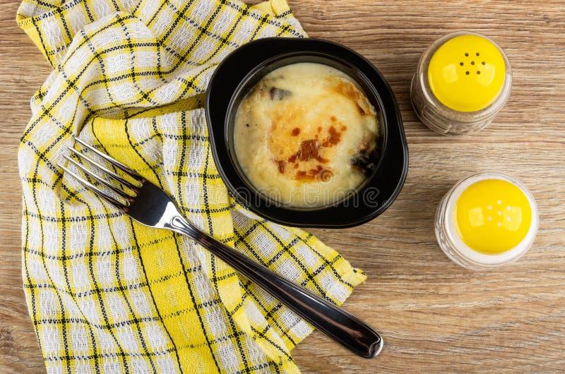 Julienne с цыпленком, грибом в шаре, салфеткой, солью и перцем, вилкой на деревянном столе r стоковое фото rf