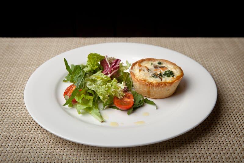 Julienne in tartlet met salade en tomaten op een witte plaat stock afbeeldingen