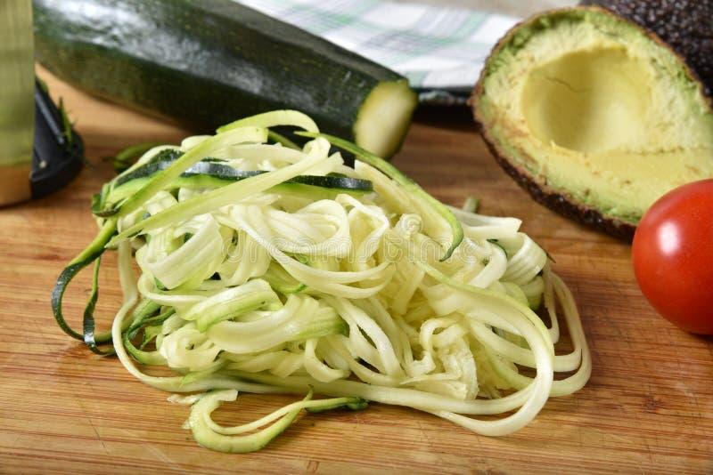 Julienned zucchini na tnącej desce z pomidorem i avocado fotografia stock