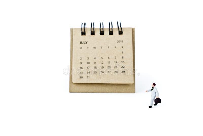 julio Haga calendarios la hoja y al hombre de negocios plástico miniatura en blanco imagenes de archivo