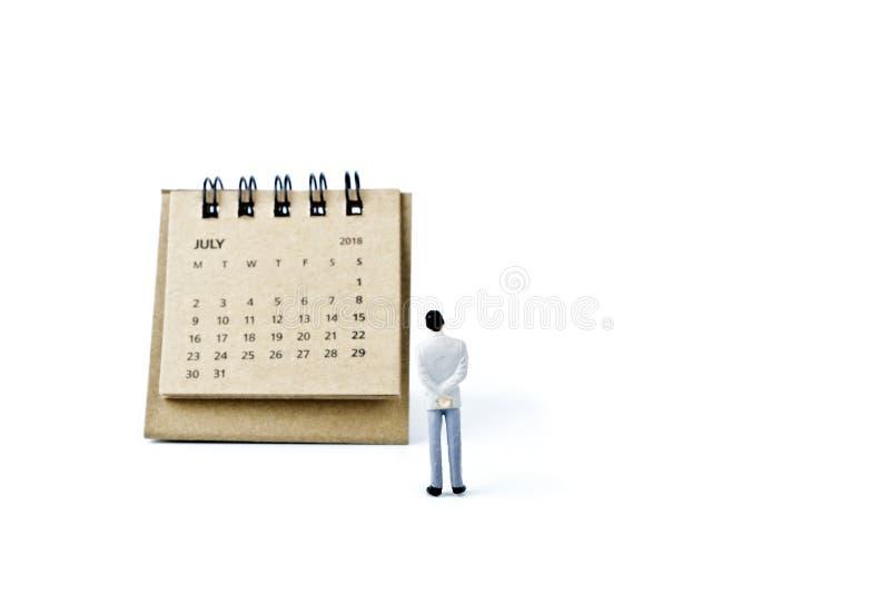 julio Haga calendarios la hoja y al hombre plástico miniatura en el backgrou blanco foto de archivo libre de regalías