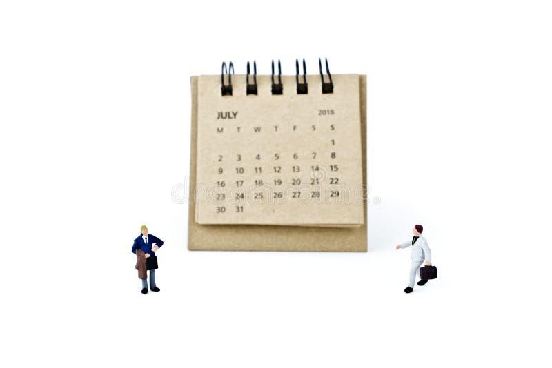 julio Haga calendarios la hoja y a los hombres de negocios plásticos miniatura en blanco imagenes de archivo