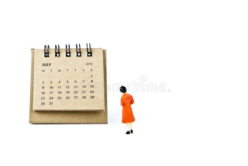 julio Haga calendarios la hoja y a la mujer plástica miniatura en el backgr blanco fotos de archivo