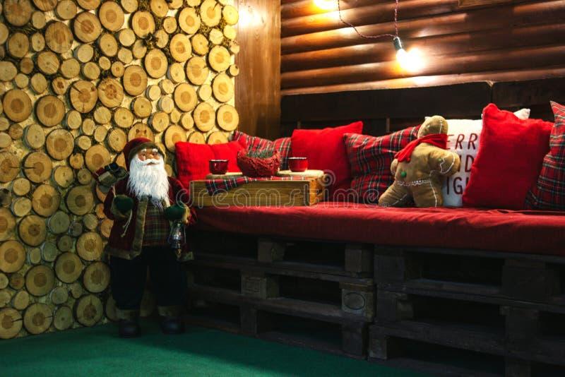 Juljultomten, träröda kuddar och prydnader Säng av paletter royaltyfri foto