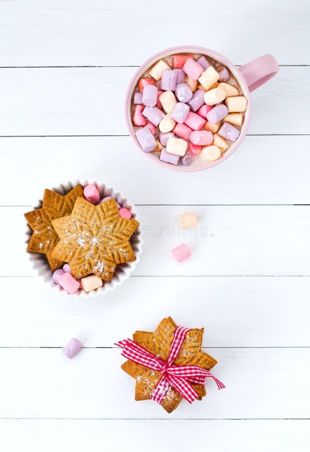 Julkakao med marshmallowrosa färgkoppen och ingefärakexet på en trätabell fotografering för bildbyråer