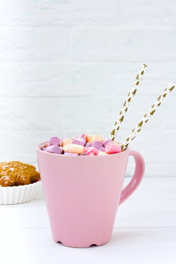 Julkakao med marshmallowrosa färgkoppen och ingefärakexet på en trätabell arkivfoton