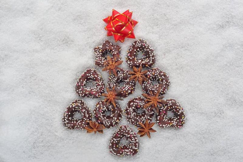 Julkakaträd som överst göras av kanel med en röd stjärna på en snöig bakgrund royaltyfri fotografi