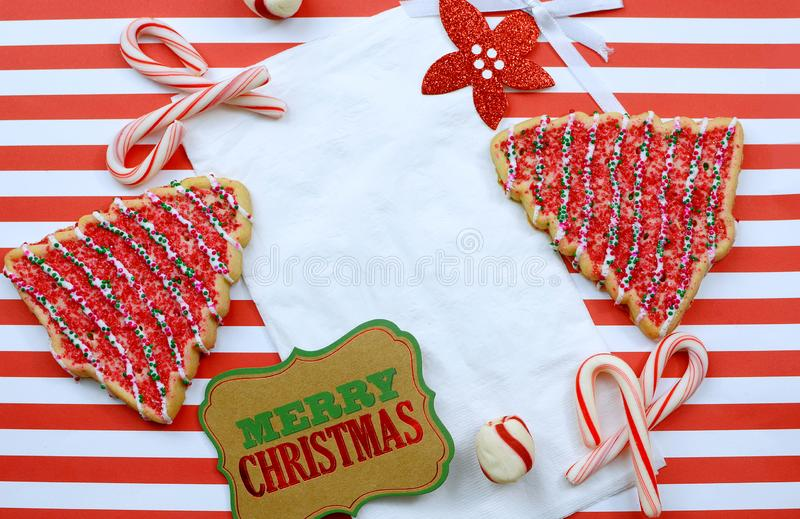 Julkakor och dekoration omger en vit napkin på en snål röd och vit strimlad bakgrund royaltyfri foto