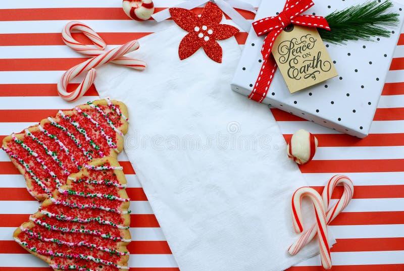 Julkakor och dekoration omger en vit napkin på en snål röd och vit strimlad bakgrund fotografering för bildbyråer