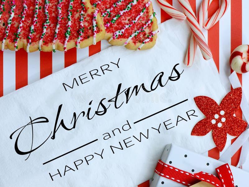 Julkakor och dekoration omger en vit napkin på en snål röd och vit strimlad bakgrund arkivbild
