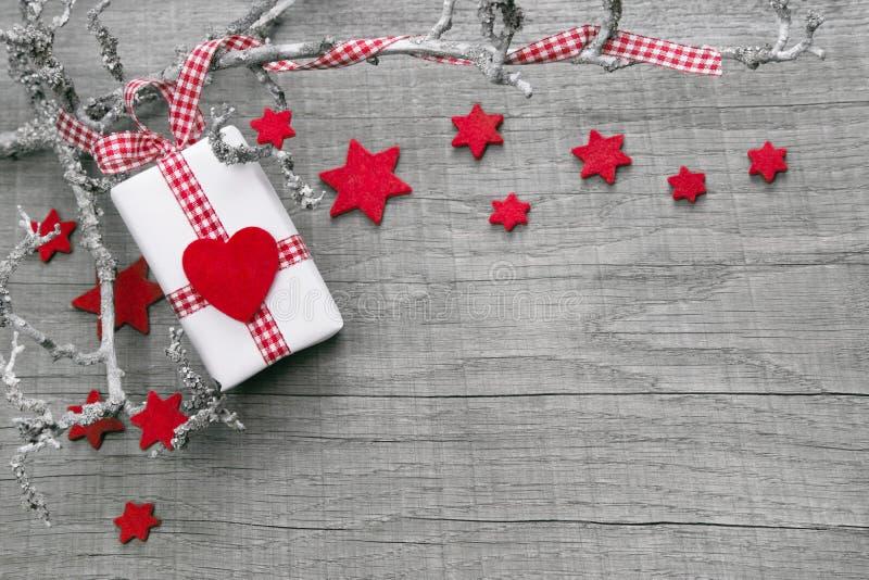 Julklapp som slås in i rött papper på en träbakgrund fotografering för bildbyråer
