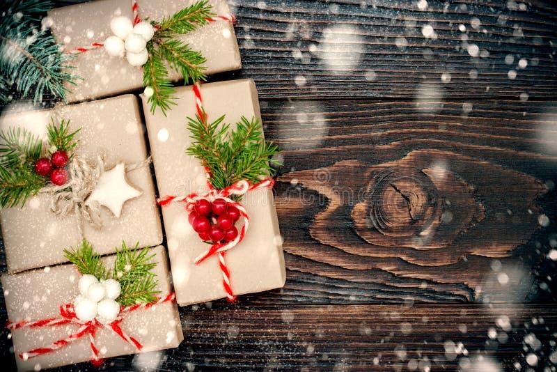 Julklappar i askar på en träbakgrund med kopieringsutrymme Utdraget snöfall royaltyfri foto
