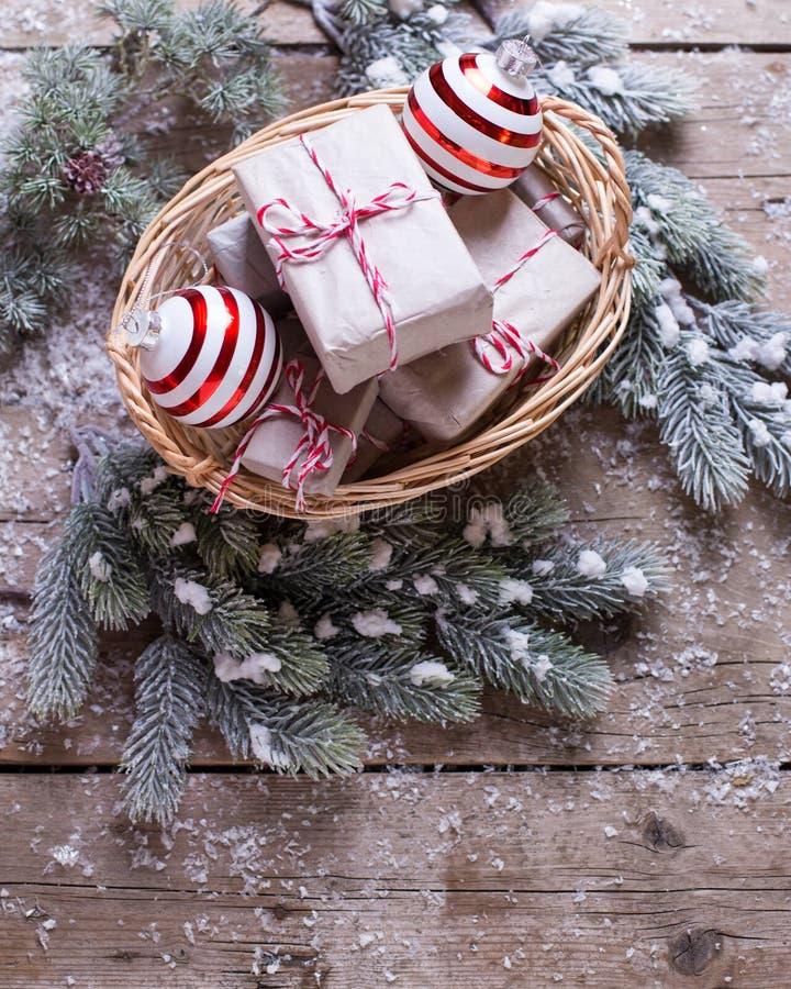 Julklappar i korg, pälsträd och dekorativ balsl på a arkivfoton