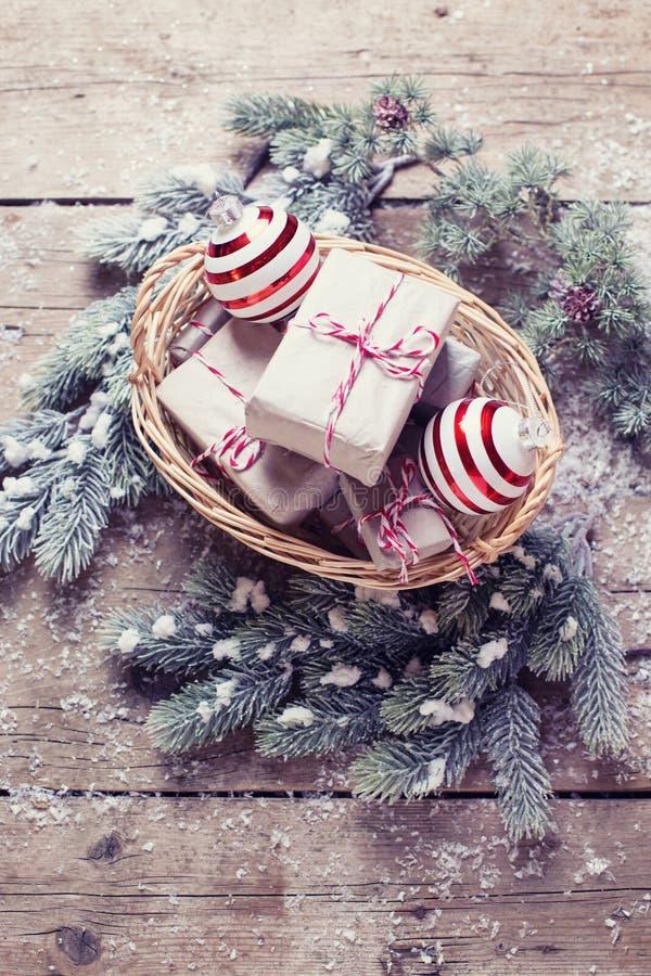 Julklappar i korg, pälsträd och dekorativ balsl på a arkivbild