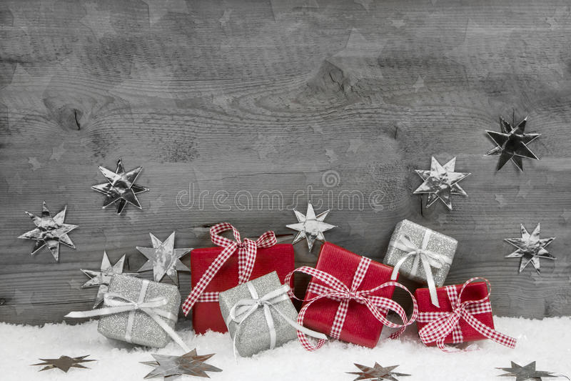 Julklappar i rött och silver på trägrå bakgrund royaltyfri foto