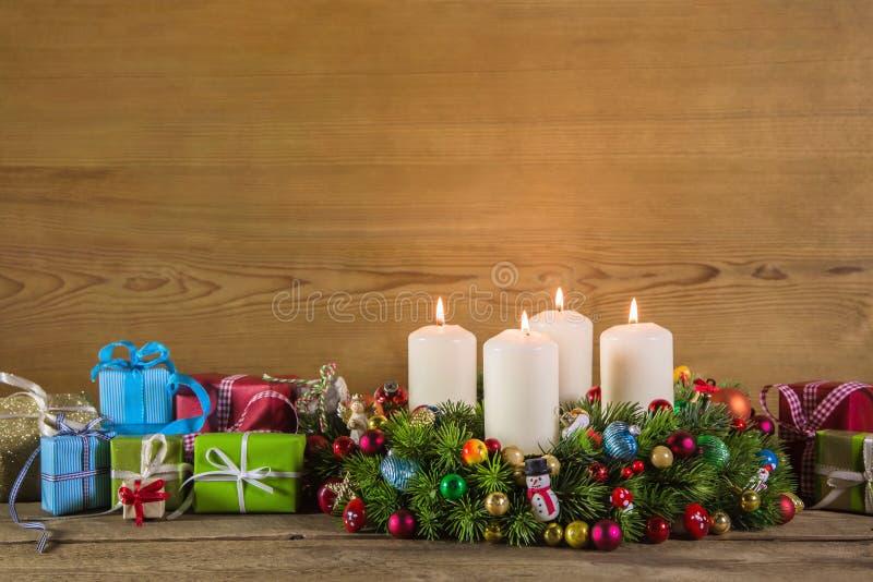 Julklappar och adventkrans på träfärgrik backgrou arkivfoton