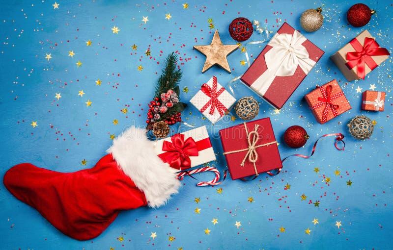 Julklappar som flödar ut ur strumpa för jultomten` s arkivbild