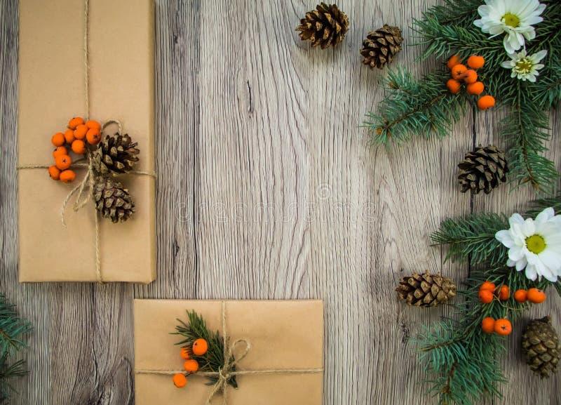 Julklappar som slås in i kraft papper med naturlig garnering Lekmanna- lägenhet, bästa sikt royaltyfri foto