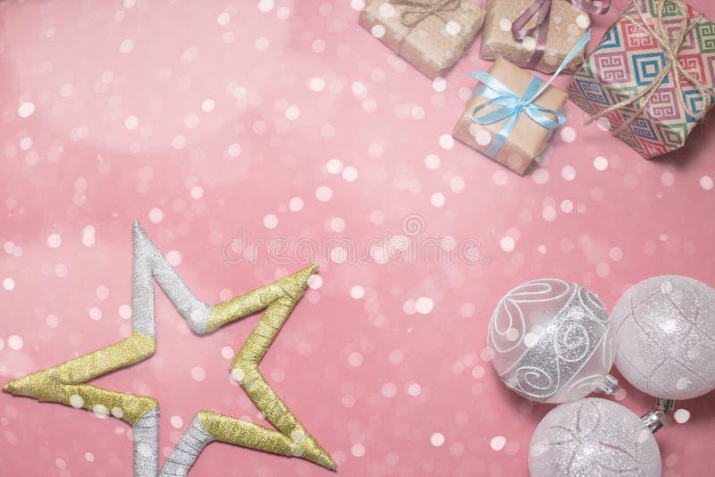 Julklappar, vitbollar och stjärna på rosa färgtabellen Lägenheten lägger med kopieringsutrymme Julkort i vaniljstil royaltyfria bilder