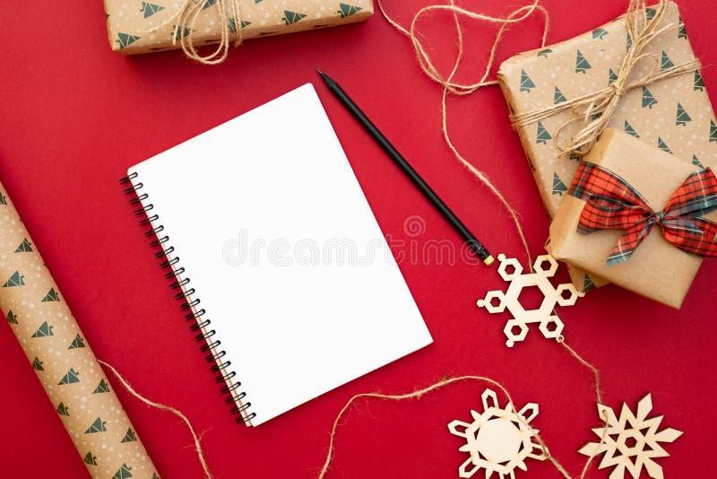 Julklappförberedelse Anteckningsboken blyertspennan, gåvor som packas i hantverkpapper, dekorativa snöflingor, tvinnar på röd bak arkivfoton
