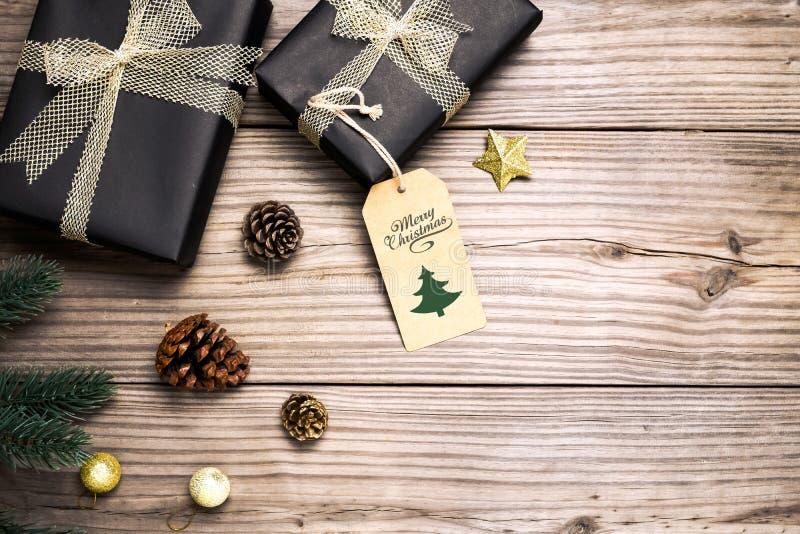 Julklappgåvaask och lantlig garnering på tappningträbakgrund arkivbild