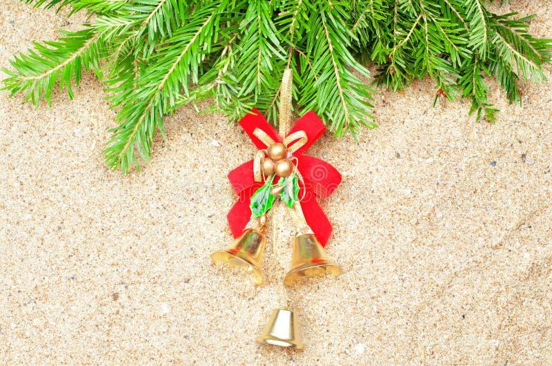 Julklockor och granträd i sanden royaltyfri foto