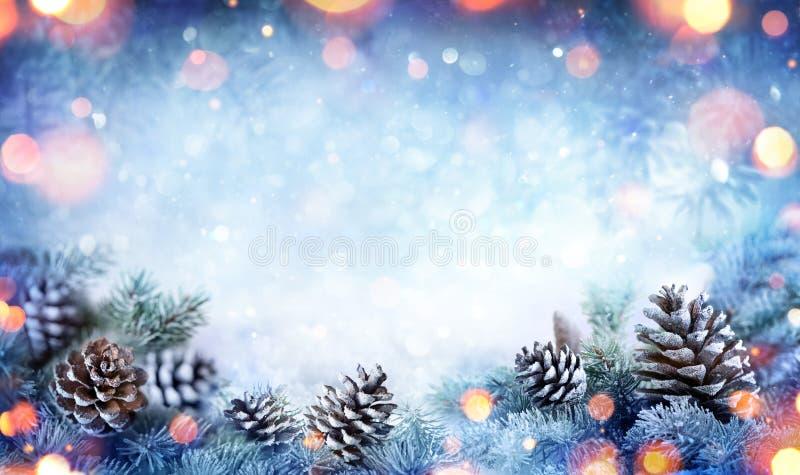 Julkort - den snöig granfilialen med sörjer kottar royaltyfria bilder
