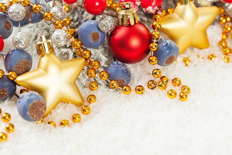 Julkort med den guld- girlanden, stjärnor, järnekbär och att blänka dekoren på vit snöbakgrund royaltyfria foton