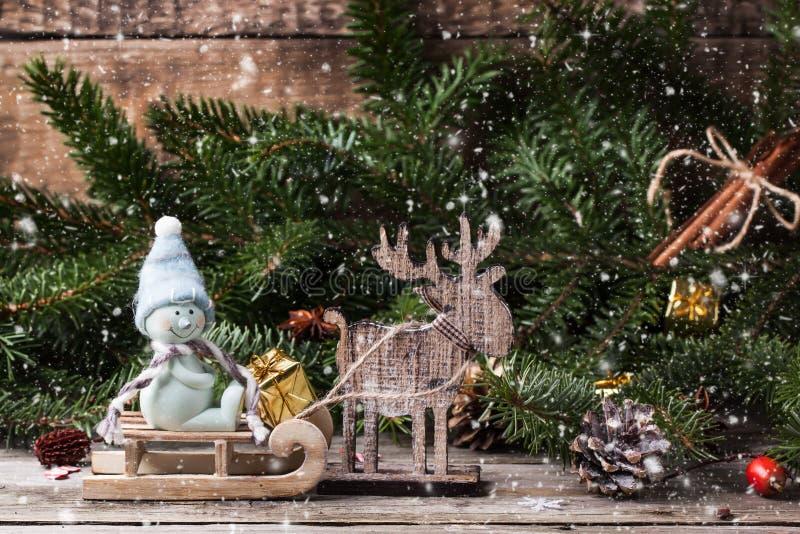 Julkort med snögubben och hjortar royaltyfria bilder