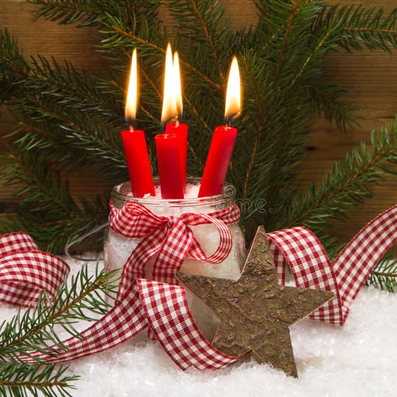 Julkort som dekoreras med fyra röda bränningstearinljus fotografering för bildbyråer