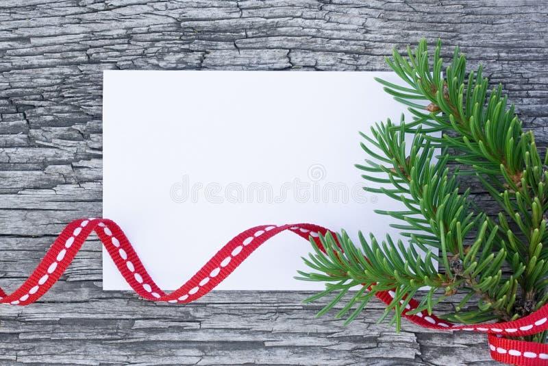 Julkort: tomt papper med gran-trädet förgrena sig på träbakgrund royaltyfri bild
